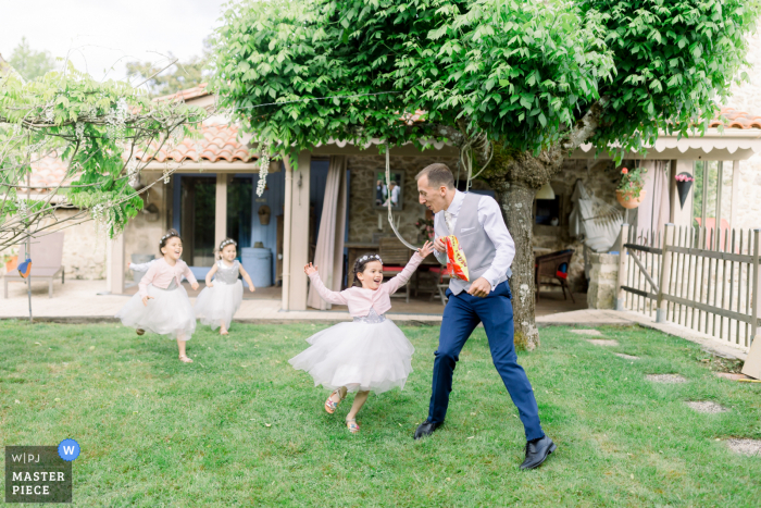 A wedding photographer in Bordeaux, France created this image ofthe Groom playing with kids during the outdoor garden reception