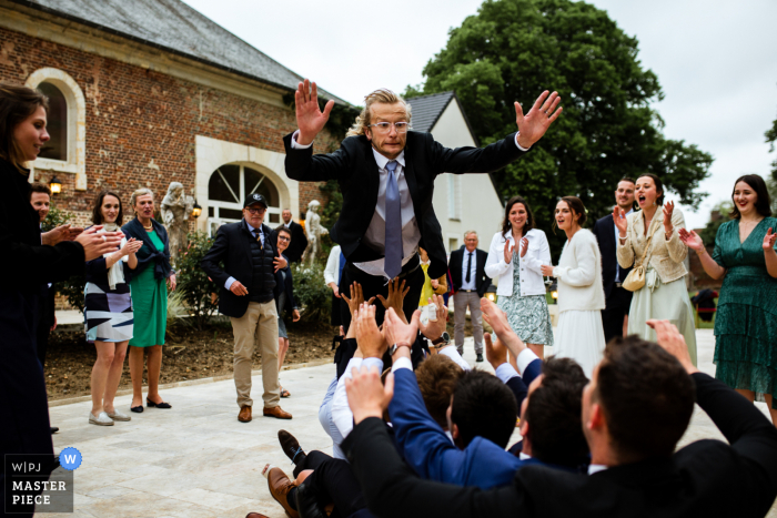 A top wedding photographer in Paris captured this picture ofA great jump by the groom into the hands of men