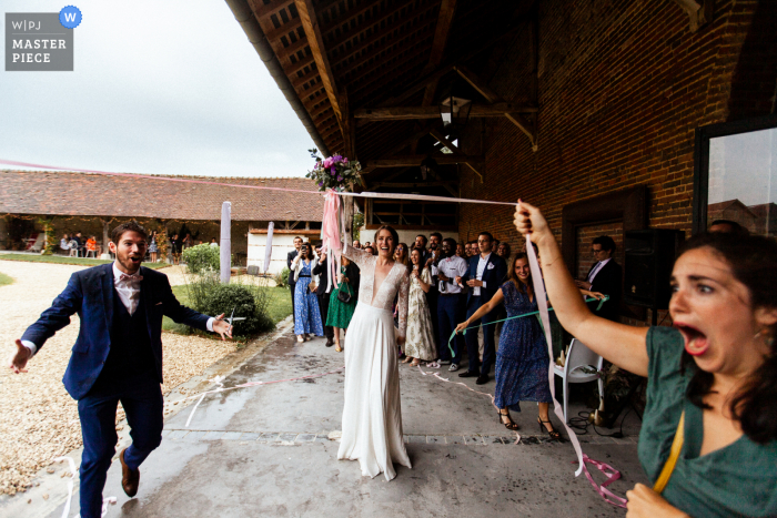 A top wedding photographer in Paris captured this picture showing A girl is getting close to getting the bouquet
