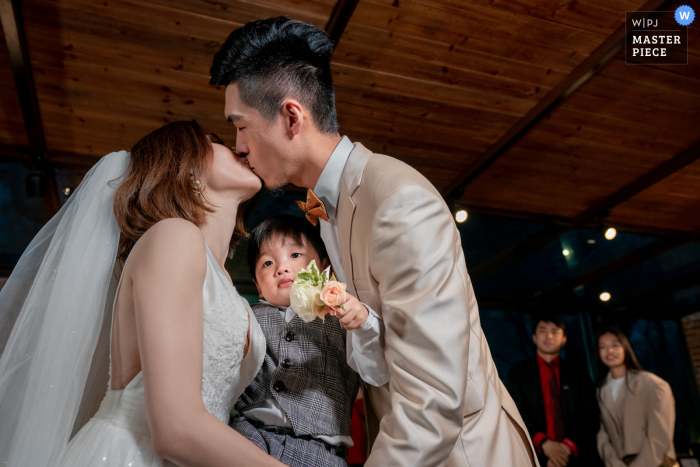 A wedding photographer in Taipei created this image ofThe couple kissing at the ceremony holding their son