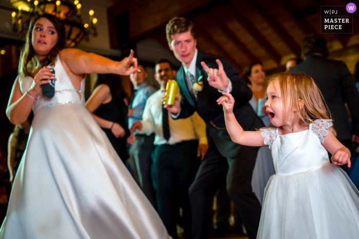 A top Charlottesville, VA wedding photographer at Mt. Ida Farm captured this picture showing A flower girl strikes a dance move with the bride and groom