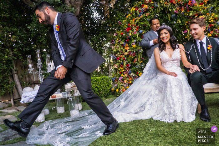 A wedding photographer at the Lombardi House in Los Angeles created this image showing A brother of the bride walks over the veil of her dress during the ceremony.