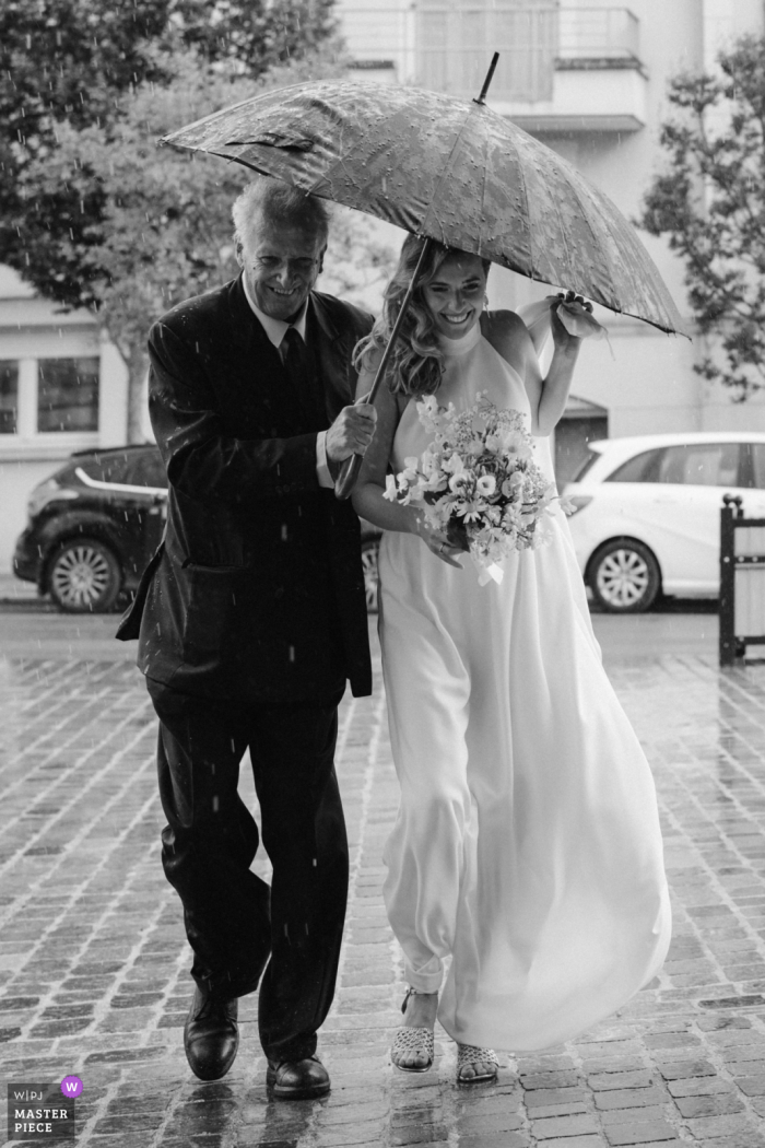 Church in Clamart near Paris wedding photography showing Just as the bride got out of the car, the heavens opened and it started pouring down with rain, Along with her dad, she made a run for the church entrance
