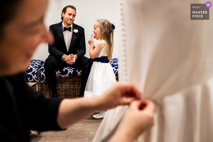 Wychmere Beach Club, Harwich, MA wedding photography of The flower girl eating a lollipop while the bride gets bustled