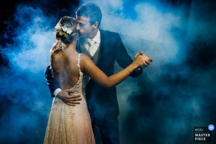 Rio Grande do Sul wedding image of bride and groom dancing under blue lights and fog