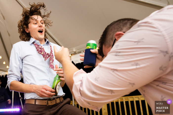 Virginia wedding photography of a Guest bowing down to Grooms amazing air guitar skills