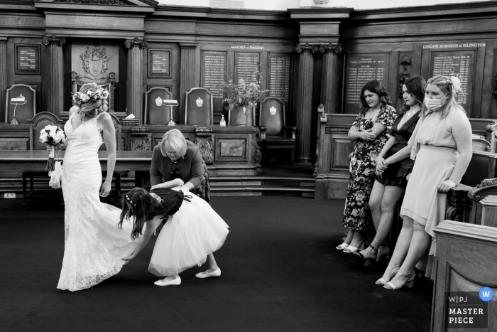 Hackney Town Hall indoor marriage ceremony award-winning image showing the Last minute alterations in black and white. The world's best wedding picture competitions are featured via theWPJA