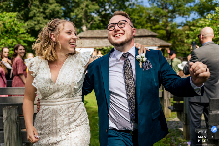 Cacapon State Park, West Virginia outdoor marriage ceremony award-winning image showing the Couple joyfully exits under trees and blue skies. The world's best wedding photo contests presented by the WPJA