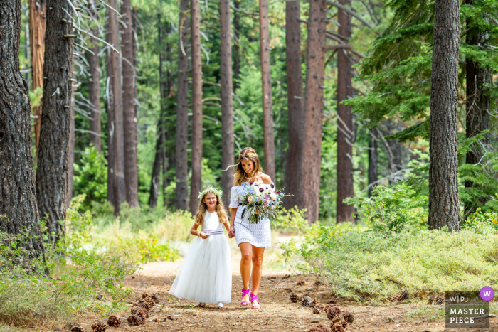 Skylandia, Lake Tahoe, California outdoor marriage ceremony award-winning image showing the Bride and flower girl walking down the wedding aisle. The world's best wedding photo contests presented by the WPJA