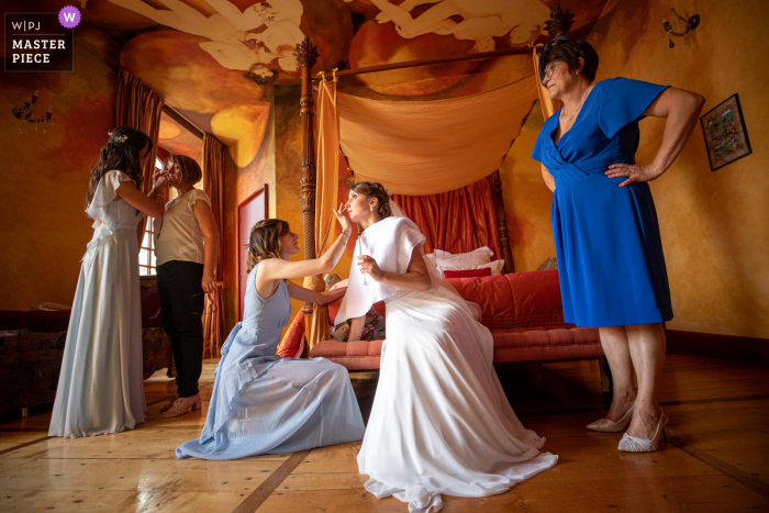 Occitanie marriage preparation time award-winning picture capturing the Retouch of make up before church after a lot of emotion. The world's best wedding image competitions are held by the WPJA