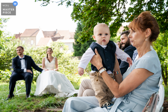 Couches, France outdoor marriage reception party award-winning photo that has recorded a baby having Seasickness