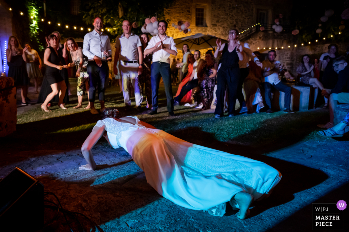 Montpellier, France outdoor marriage reception party award-winning photo that has recorded the bride doing push-ups during the wedding. The world's top wedding photographers compete at the WPJA