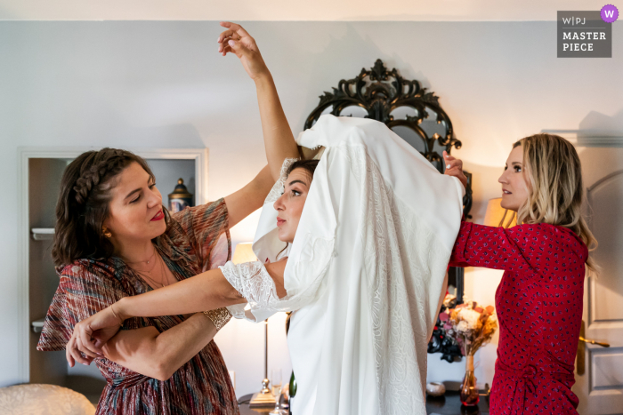 Montpellier, France marriage preparation time award-winning picture capturing the bride getting helped into her dress. The world's best wedding image competitions are held by the WPJA