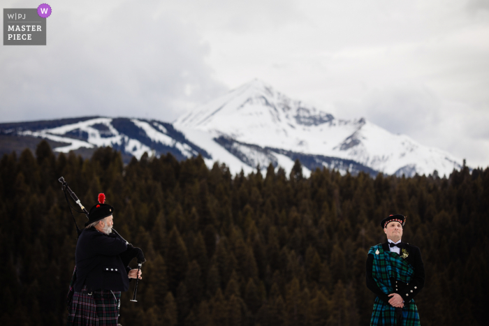 Big Sky, Montana nuptial day award-winning image of the groom getting emotional listening to bagpiper before processional. The world's best wedding photography competitions are hosted by the WPJA