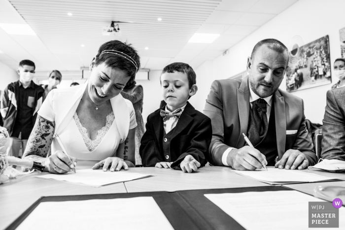 Brittany indoor marriage ceremony award-winning image showing the bride and grooms son when the couple sign