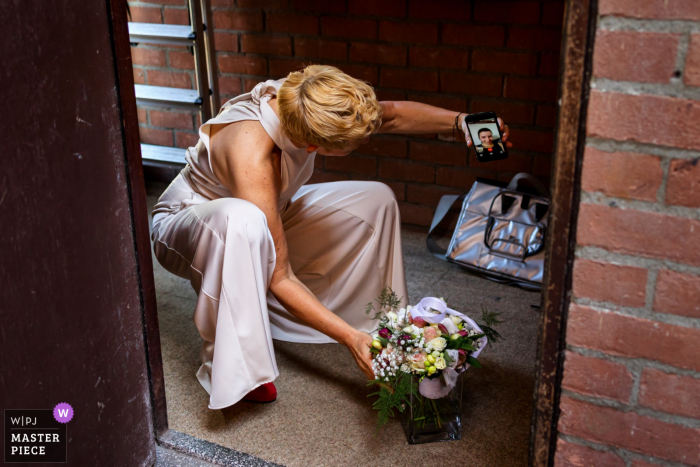 Amsterdam nuptial day award-winning image of the mom showing her self-made flower bouquet to friend in a videocall. The world's best wedding photography competitions are hosted by the WPJA