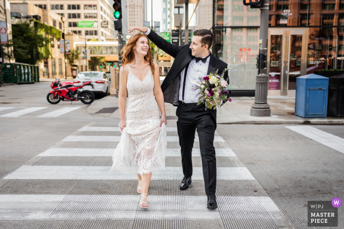 Chicago nuptial day award-winning image of the couple crossing the street while the groom holds the bouquet and fixes the bride's hair. The world's best wedding photography competitions are hosted by the WPJA