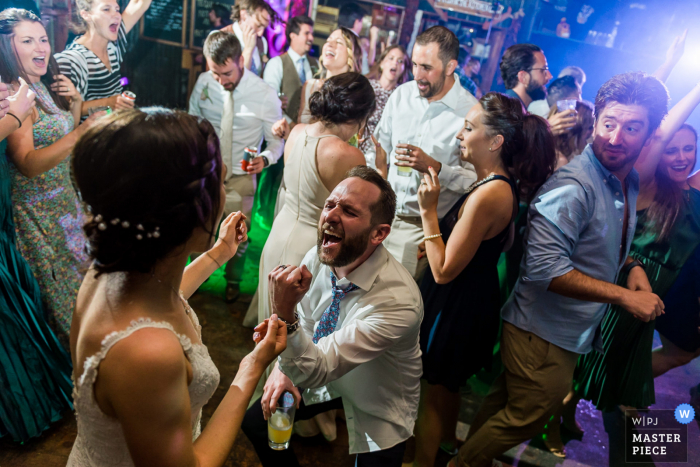 Bonez - Crested Butte, CO indoor wedding reception party award-winning picture showing a groom sings his heart out on the dancefloor to his wife. The world's most skilled wedding photographers are members of the WPJA