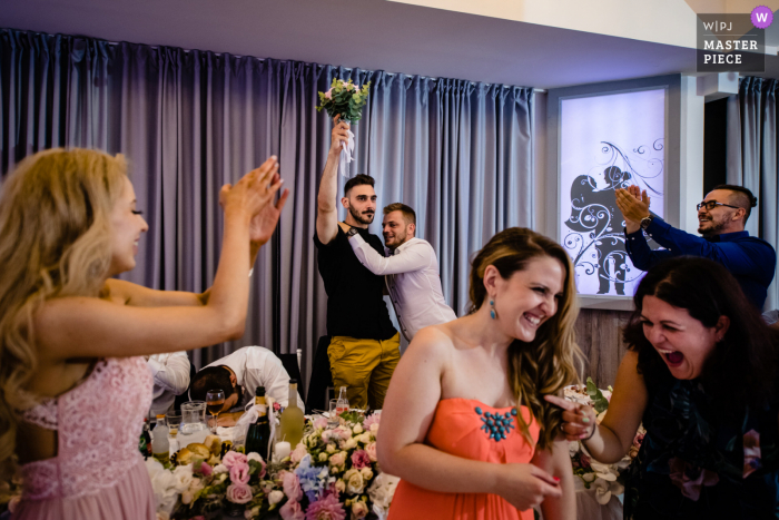 Hotel Akord, Sofia indoor wedding reception party award-winning picture showing a young man accidentally grabbing the bouquet. The world's most skilled wedding photographers are members of the WPJA
