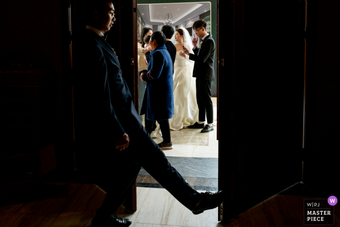 Sichuan indoor marriage ceremony award-winning image showing The wedding ceremony is about to begin. This is the door where the bride enters the auditorium at the beginning of the ceremony. The best man is closing the door to prepare for the ceremony.