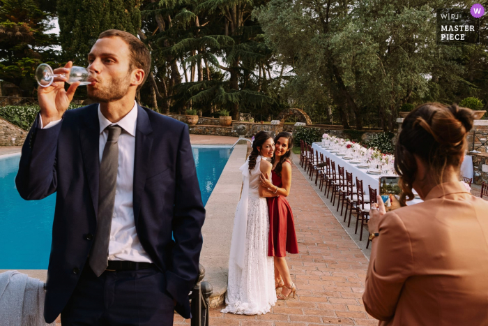 Borgo della Merluzza, Rome outdoor marriage reception party award-winning photo that has recorded the bride getting her picture taken with friends whilst a guest in drinking in the foreground. The world's top wedding photographers compete at the WPJA
