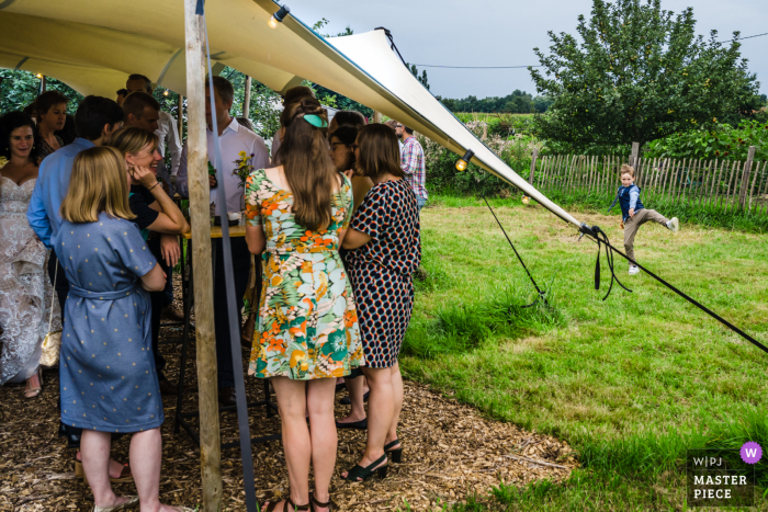 Limburg outdoor marriage reception party award-winning photo that has recorded Kids having fun at the tent
