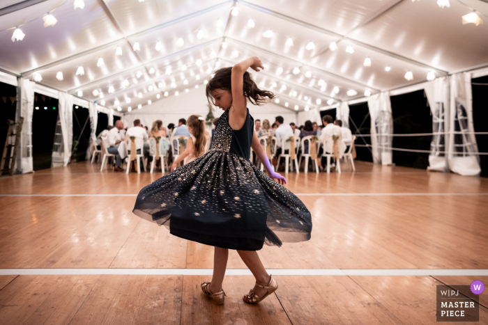 Chateau du Vergnet, Tarn outdoor marriage reception party award-winning photo that has recorded a little girl dancing while everybody is eating. The world's top wedding photographers compete at the WPJA