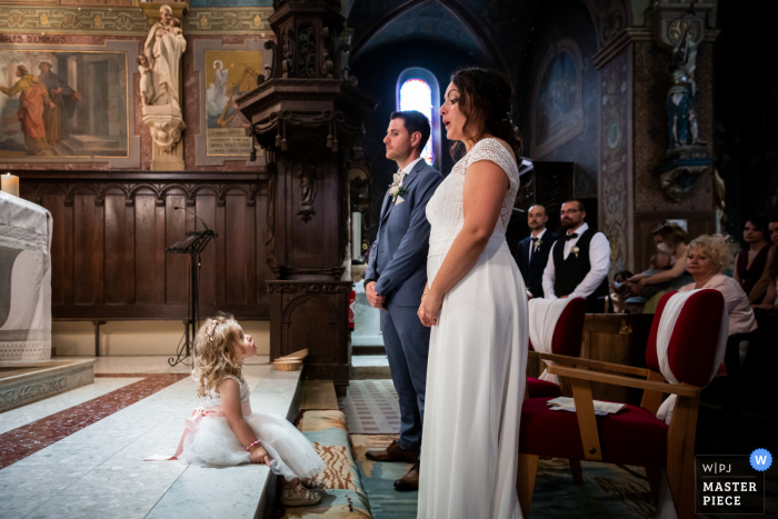 Sainte Cécile de Fréjairolles church indoor marriage ceremony award-winning image showing a cute moment between the bride and her daughter at the church. The world's best wedding picture competitions are featured via theWPJA