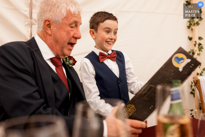 Lake District, United Kingdom indoor wedding reception party award-winning picture with a Page Boy showing Grandad his wedding gift