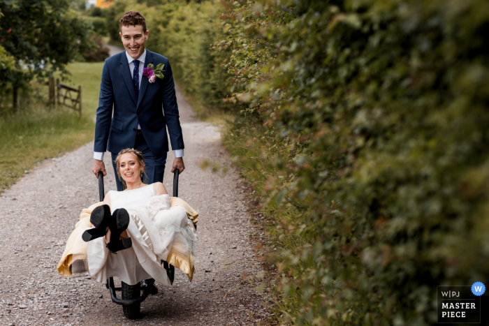 Chiltern Open Air Museum, UK nuptial day award-winning image of the Bride being ferried to reception in wheel barrow