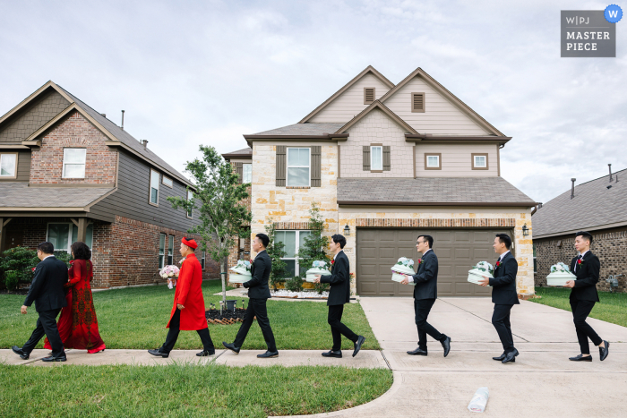 Texas nuptial day award-winning image of the groomsmen helping the groom bring gifts to the bride's family. The world's best wedding photography competitions are hosted by the WPJA