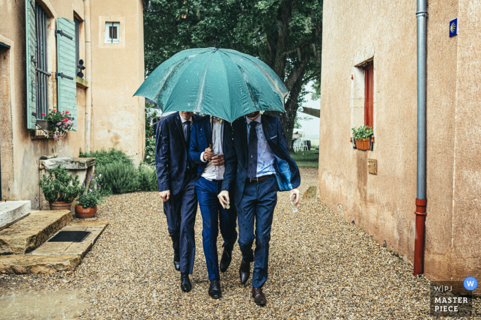 Beaujolais nuptial day award-winning image of Guests sheltering from the rain