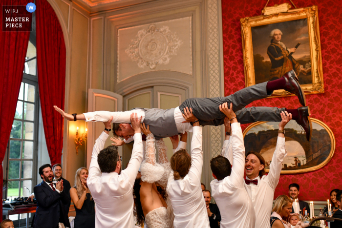 Lille indoor wedding reception party award-winning picture showing The bride and groomsmen who hold the groom after their entrance dance
