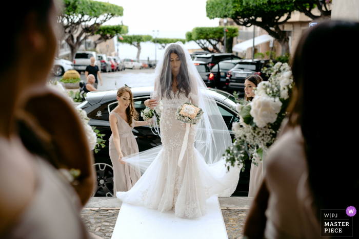 Italy nuptial day award-winning image of the bride adjusting her veil outdoors before entering the church
