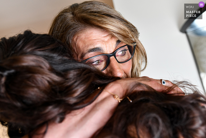 France nuptial day award-winning image of The mother extremely moved in the arms of the bride