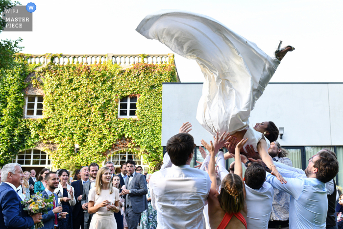 Lille outdoor marriage reception party award-winning photo that has recorded the bride's relatives trying to throw her in the air