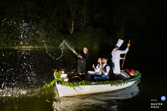 Brittany, Rennes outdoor marriage reception party award-winning photo that has recorded the arrival of the cake and champagne via a boat. The world's top wedding photographers compete at the WPJA