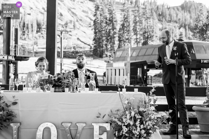 Sugarbowl Resort, Truckee, CA outdoor marriage reception party award-winning photo that has recorded A groom reacting with surprise to his best man's speech while his wife laughs