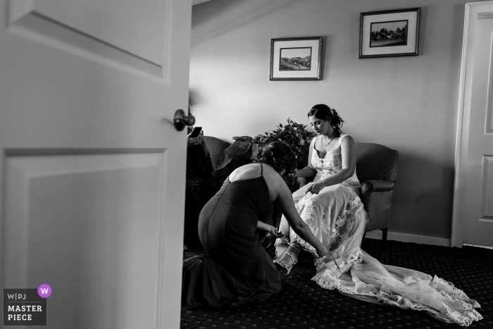 Bar Harbor, Maine marriage preparation time award-winning picture capturing A bridesmaid helps a bride put on her shoes on. The world's best wedding image competitions are held by the WPJA