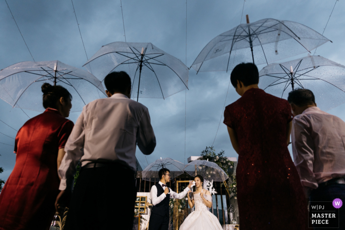 Guangdong nuptial day award-winning image of an outdoor wedding in the rain under umbrellas. The world's best wedding photography competitions are hosted by the WPJA