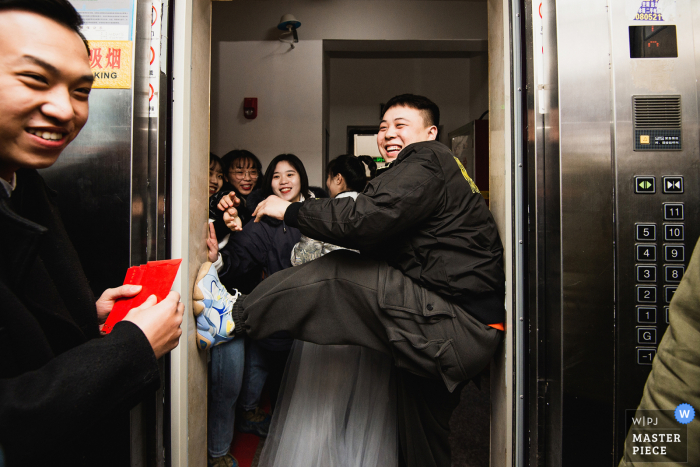 Fujian nuptial day award-winning image of Relatives and friends preventing the groom from entering the new house