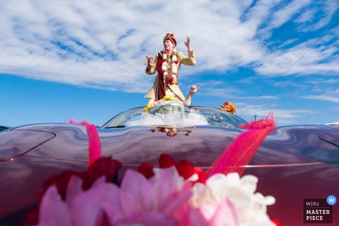 The Roostertail, Detroit, MI nuptial day award-winning image of The grooms baraat riding in on a Corvette.