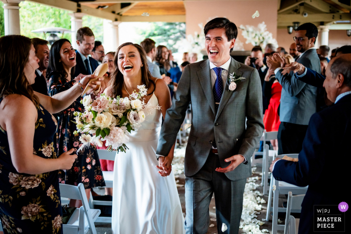 The Broadmoor Hotel, Colorado Springs indoor marriage ceremony award-winning image showing the couple Getting hit in the face with rice as they walk down the isle after getting married.