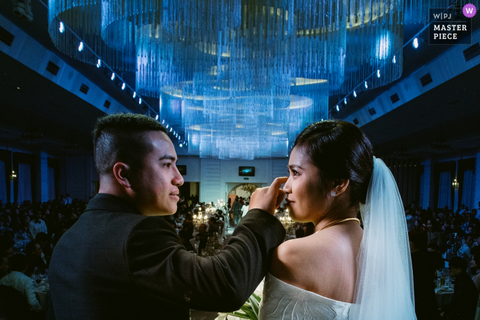 Haiphong, Vietnam indoor marriage award-winning image showing bride and groom During the ceremony. The world's best wedding picture competitions are featured via theWPJA