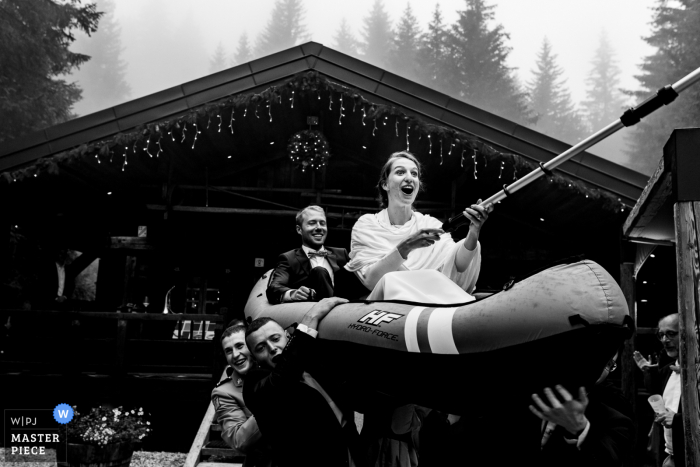 Chalet du Loup outdoor marriage reception party award-winning photo that has recorded the Couple getting carried on a canoe during cocktail hour. The world's top wedding photographers compete at the WPJA