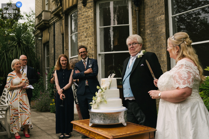Cambridge, UK outdoor marriage reception party award-winning photo that has recorded a grooms reaction to the bride holding the cake knife. The world's top wedding photographers compete at the WPJA