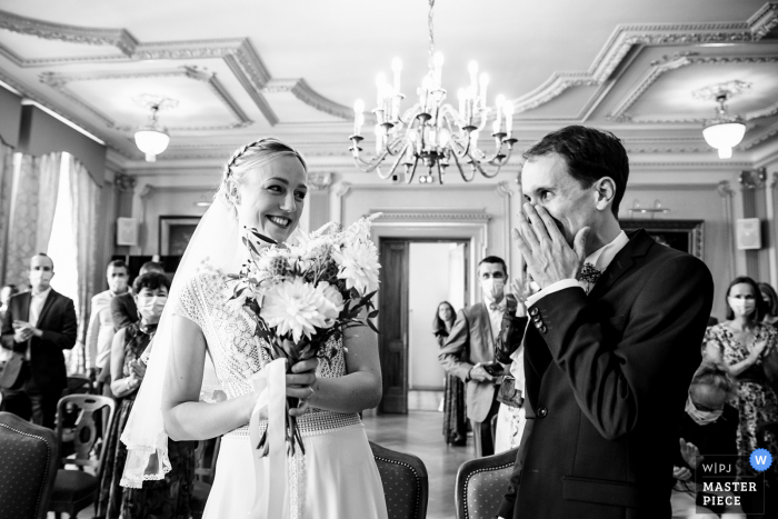 Lyon indoor marriage ceremony award-winning image showing The groom is moved to see his wife. The world's best wedding picture competitions are featured via theWPJA
