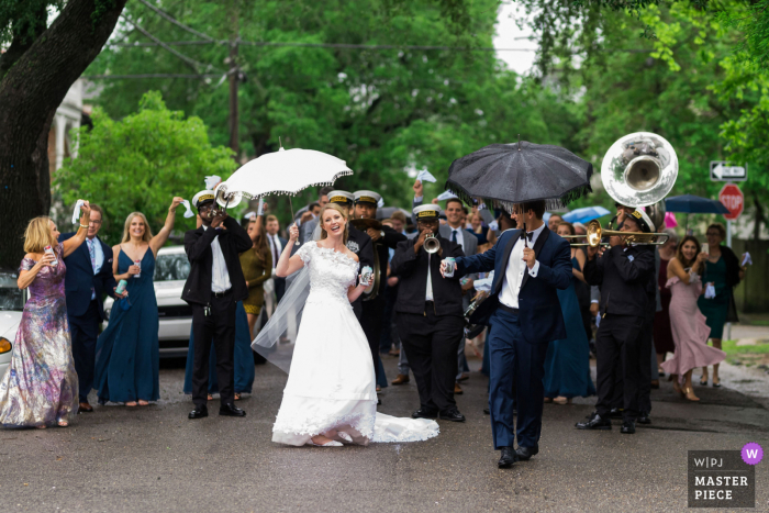 New Orleans, LA nuptial day award-winning image of A bride and groom leading the second line through the streets of uptown during their rainy April New Orleans wedding.