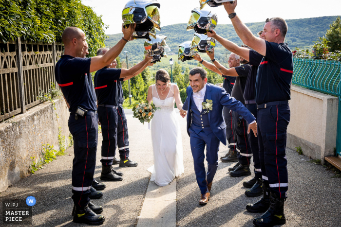 France outdoor marriage reception party award-winning photo that has recorded Firemen friends forming tunnel with helmets. The world's top wedding photographers compete at the WPJA