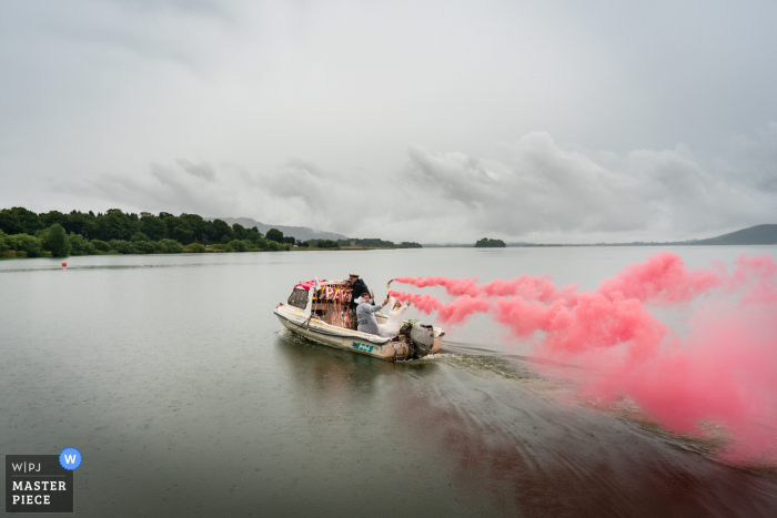 The Boathouse, Kinross outdoor marriage reception party award-winning photo that has recorded the bridal boat streaming smoke bombs. The world's top wedding photographers compete at the WPJA